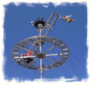 Cyber Cycle - John Winn drives his motorcycle around the aerial disk while the aerialist performs on the spinning trapeze. Copyright 2005 - 2009 Pathway International All Rights Reserved.